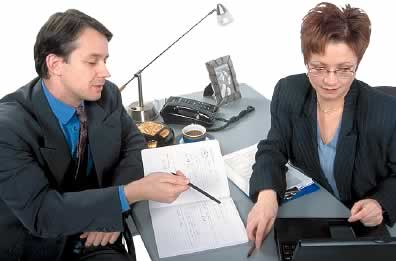 Woman at desk with laptop while man observes